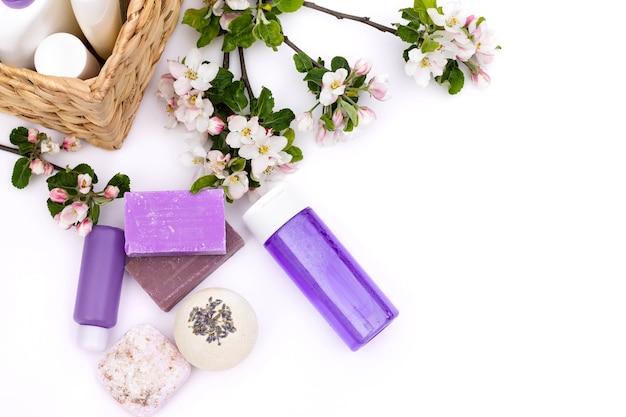 라일락 화장품 병, 목욕 폭탄, 수제 비누, 흰색 배경에 배 꽃이 있는 고리버들 바구니 근처의 목욕 소금. 천연 유기농 화장품 개념입니다. 플랫 레이