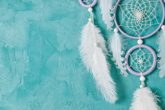 Lilac cream white dream catcher on aquamarine background. copy space for text.