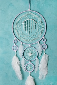Lilac cream white dream catcher on aquamarine wall. copy space for text.