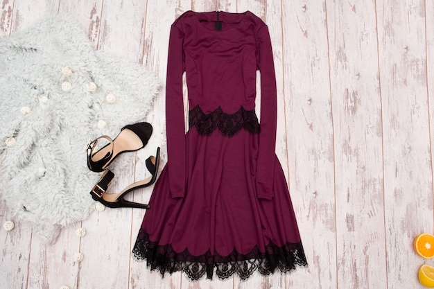 Lilac dress with lace, black shoes and a imitation fur on a wooden background