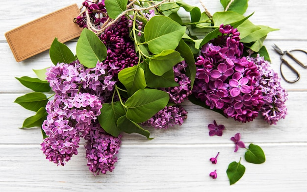 Lilac in flat style on white wooden background. beautiful spring. overhead view. flat lay, top.