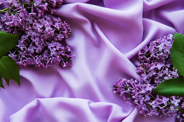 Lilac flowers on a background of lilac satin Premium Photo