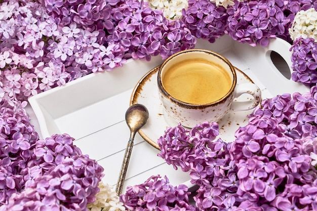 Lilac flowers background with cup of coffee in the middle with copy space.