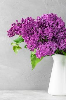 灰色のコンクリートの花瓶にライラックの花の花束