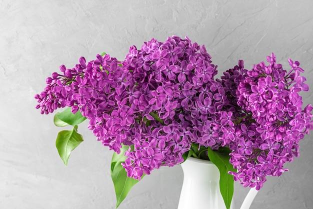 灰色のコンクリートのライラックの花の花束