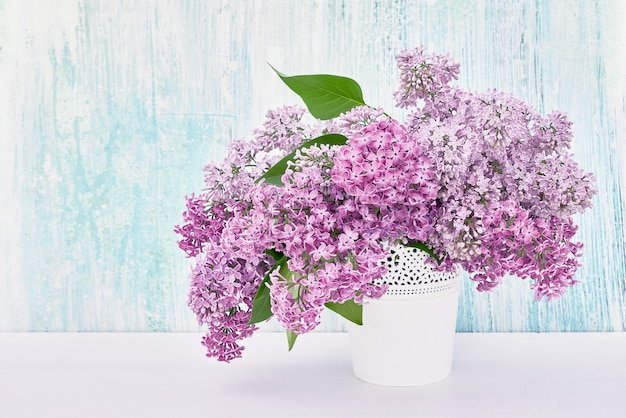 Lilac flowers bouquet in white vase on blue background.