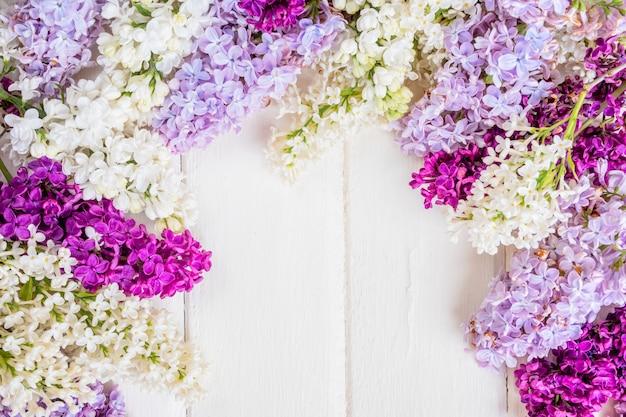 Ветвь цветов сирени на белой деревянной предпосылке с copyspace. концепция дня весны или матери