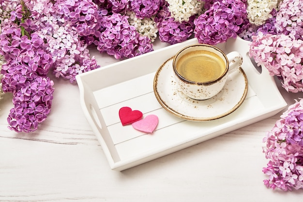 Lilac flowers and cup of coffee with hearts