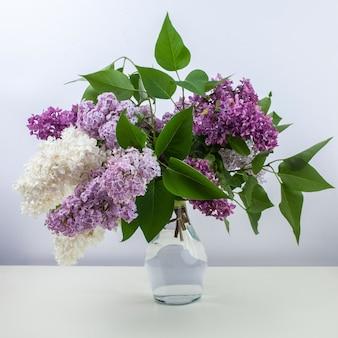 흰색 배경에 대해 유리 꽃병에 라일락 꽃