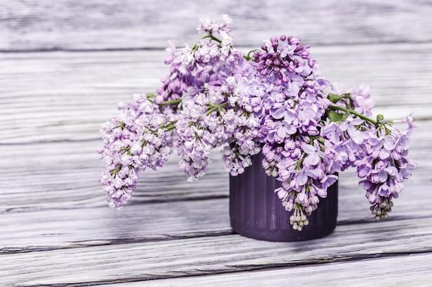 소박한 나무 배경에 유리 꽃병에 라일락 꽃