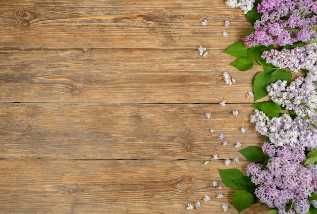 Lilac flowers on old wooden table floral background copy space