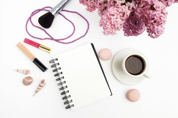 ノートとコーヒーの白い背景の上面図とワークデスク女性のホームオフィスのライラックの花