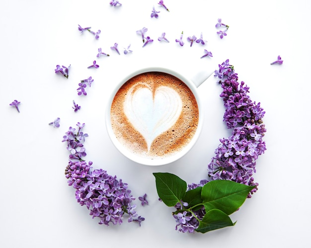 Lilac flowers on a white background in the shape of a circle top view on a cup of coffee