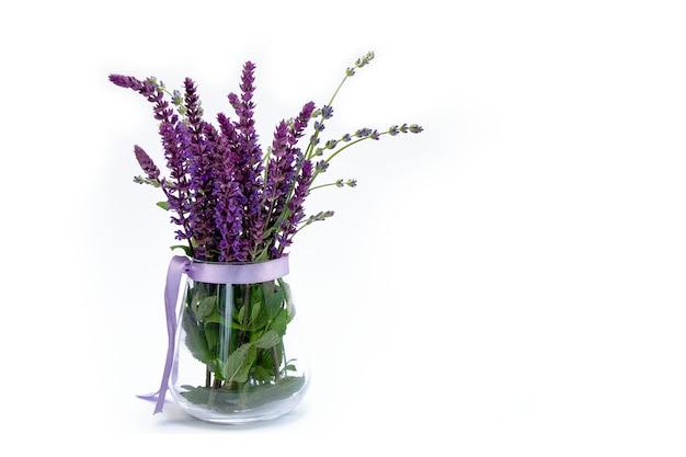 Сиреневые цветы с зелеными листьями в вазе на белом