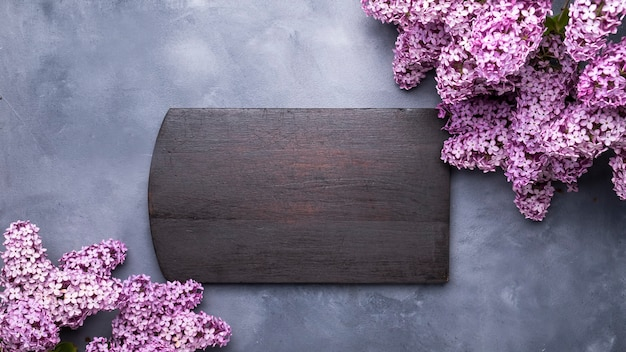Lilac flowers and wooden board. frame for text. summer time. top view