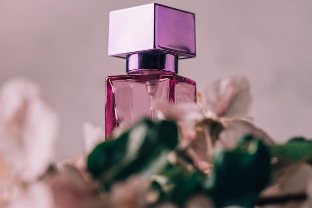 オードトワレまたは香水のライラックガラス瓶、リンゴの花が付いた軽い漆喰の表面に正方形のキャップが付いています