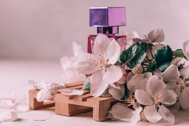 Сиреневый стеклянный флакон туалетной воды или духов с квадратной крышкой на деревянном подиуме в виде поддона на светлой штукатурке с цветами яблони