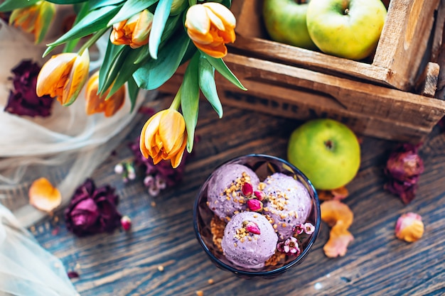 Lilac ice cream with nuts decorated with flowers. top view