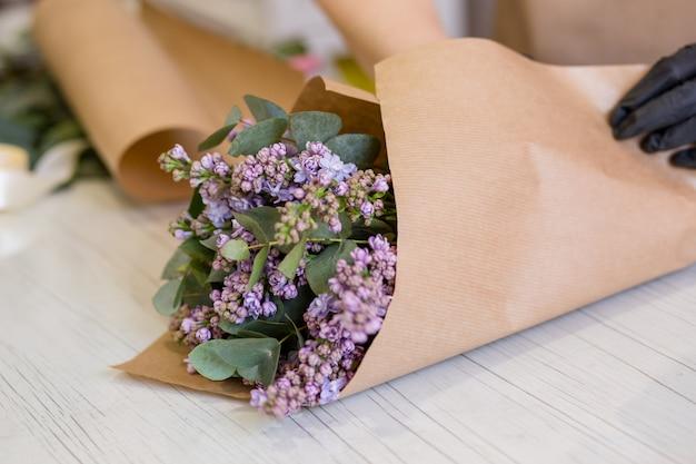 Сирень в руках цветочницы, которая создает букет в цветочном магазине