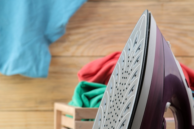 ライラック鉄と自然な木製の背景のボックス内の服のスタック。アイロンがけ。家庭用電化製品。