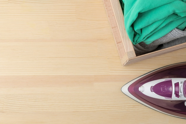 ライラック鉄と自然な木製の背景のボックス内の服のスタック。テキストの場所を含む上面図。アイロンがけ。家庭用電化製品。