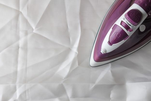 白いしわくちゃの布の家庭用電化製品のライラックアイロン。上からの眺め。