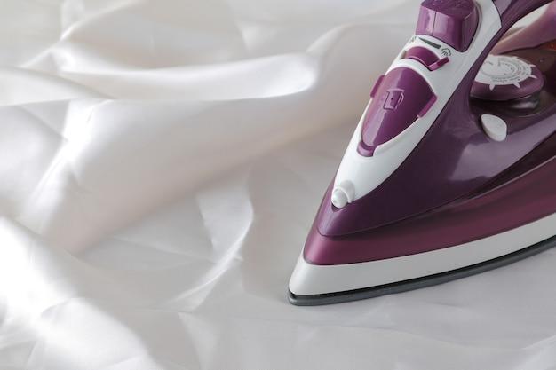 白いしわくちゃの布の家庭用電化製品のライラックアイロン。