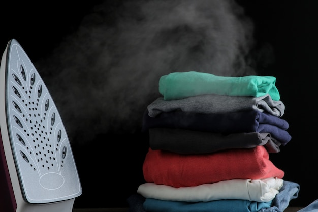 ライラック鉄は、黒い背景に蒸気と衣服のスタックを放出します。アイロンがけ。家庭用電化製品。