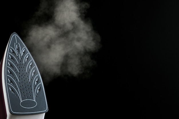 ライラック鉄は黒い背景に蒸気を放出します。アイロンがけ。家庭用電化製品。テキスト用のスペースあり