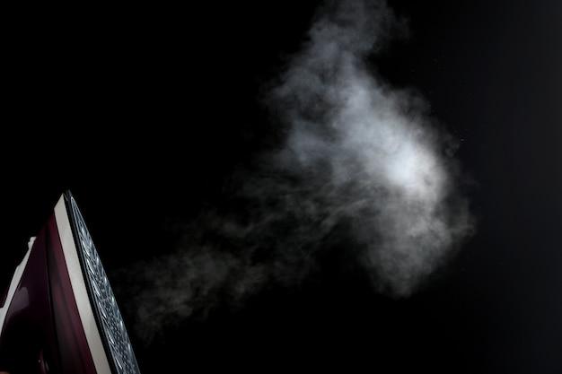 ライラック鉄は黒い背景に蒸気を放出します。アイロンがけ。家庭用電化製品。