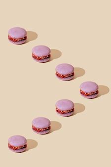 ベージュの背景にライラックマカロンパターンカラフルなフランスのデザート