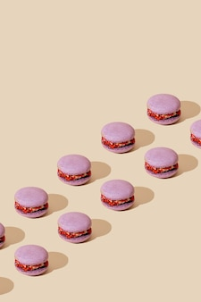 ベージュの背景にライラックマカロンパターン。カラフルなフランスのデザート。