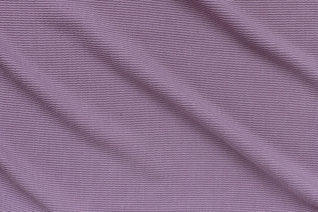 Lilac ribbed corduroy texture background with soft folds on the surface.