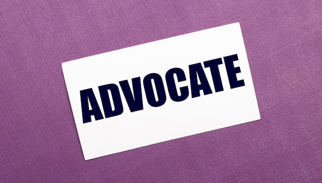 On a lilac wall, a white card with the word advocate