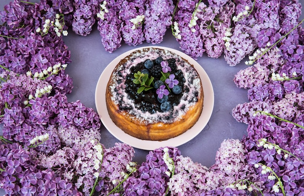Lilacs and lilies of the valley are lined with a frame and a cake with blueberries