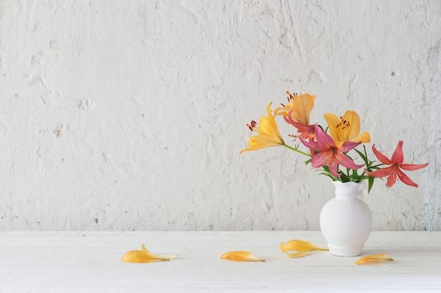 Лилии в белой вазе на белом фоне