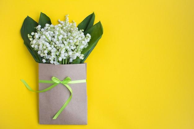 黄色の緑のリボンで結ばれた封筒の谷のユリ