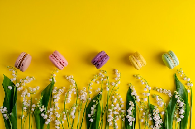 Lilies of the valley and colorful macaroons on yellow.