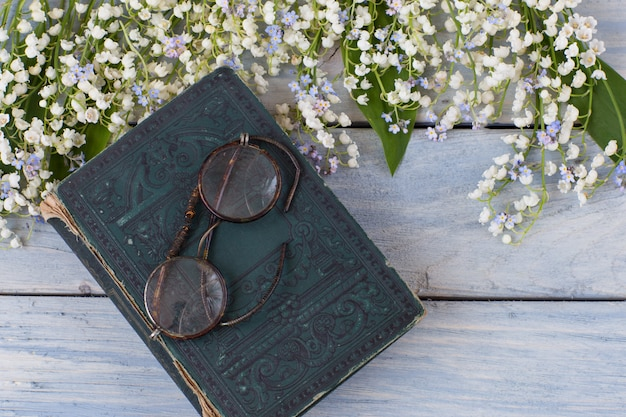 Lilies of the valley and forget me nots, old book and glasses