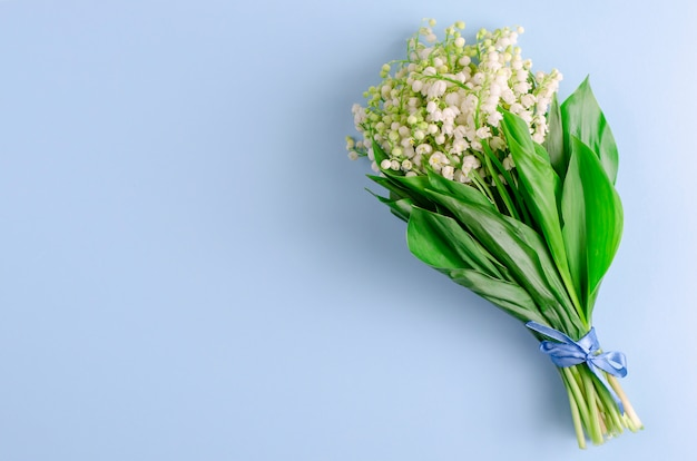 Lilies of the valley on pastel blue. copy space. spring flowers concept