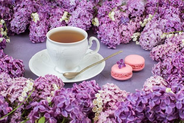 Lilies of the valley, tea in an old cup and macaroons