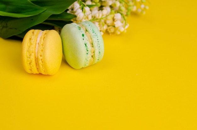 Lilies of the valley tied with ribbon and macaroons on yellow.