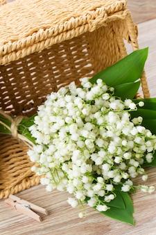 Букет цветов ландыша в корзине на деревянных фоне