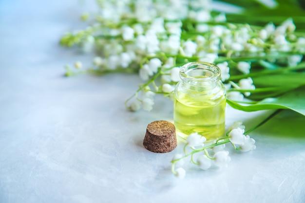 작은 병에 은방울꽃 에센셜 오일. 선택적 초점. 자연.
