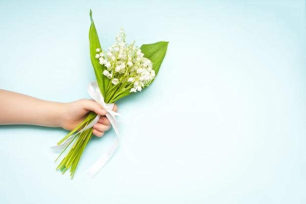 スズランの花。青色の背景にユリの谷の花の花束を持っている子手。フラット横たわっていた、トップビュー、コピースペース。
