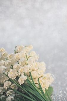 スズランの花は、明るい灰色の背景に選択的に焦点を当ててクローズアップします。自然の概念の美しさ。コピースペースのあるカード。