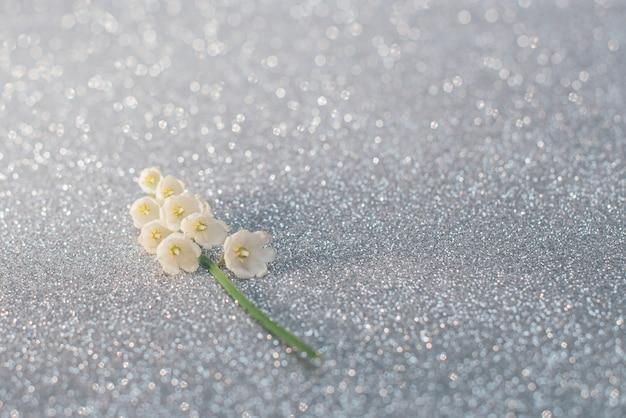 スズランの花は、明るい銀色の背景に選択的に焦点を当ててクローズアップします。自然の概念の美しさ。コピースペースのあるカード。