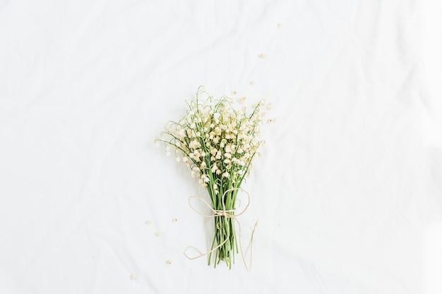 白い背景にスズランの花。フラットレイ、トップ ビュー