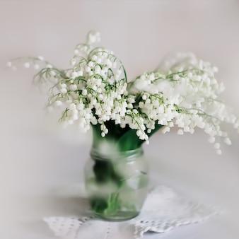 白い背景の上のガラスの花瓶の谷のユリ。春の花。バレンタインデー、春、3月8日のコンセプト
