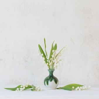 표면 오래 된 흰 벽에 작은 꽃병에 은방울꽃